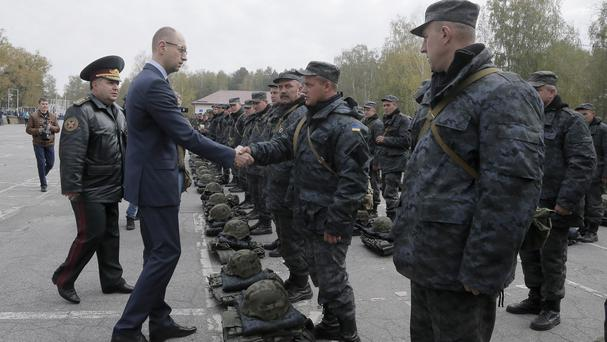 Ukrainian prime minister Arseniy Yatsenyuk greets soldiers setting out for eastern Ukraine. (AP)