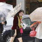 Pedestrians make their way through a street in Tokyo before a powerful typhoon hit (AP/Kyodo News)