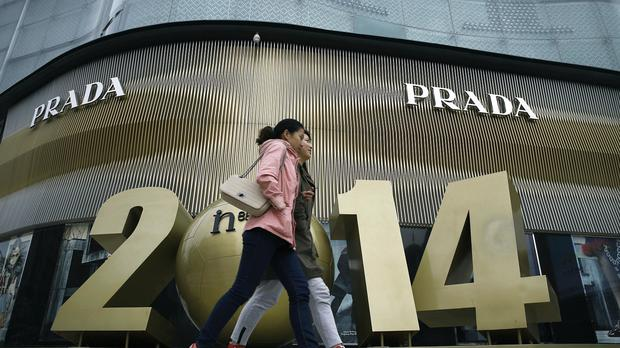 Chinese women walk past a luxury fashion boutique at a shopping mall in Beijing (AP)