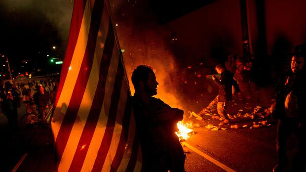 A protester holds a US flag at a demo in Oakland, California, over the grand jury decision not to indict Ferguson police officer Darren Wilson in the fatal shooting of Michael Brown (AP)