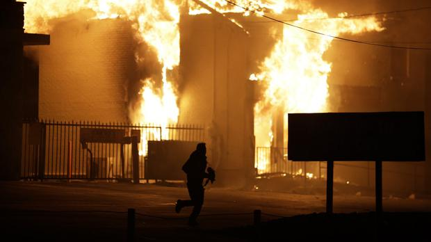 A man runs away from the burning storage facility after the announcement of the grand jury decision over the death of Michael Brown in Ferguson, Missouri (AP)