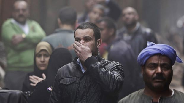 Relatives react as they wait near the rubble in the Cairo suburb of Matariya (AP)