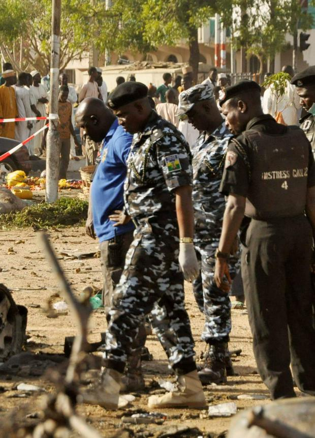 Bomb detection security personnel inspect the wreckage of a car believed to be used in the Kano Central Mosque bombing