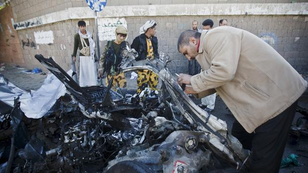 A police investigator collects evidence from wreckage at the scene of a car bomb outside a police academy in Sanaa, Yemen (AP)