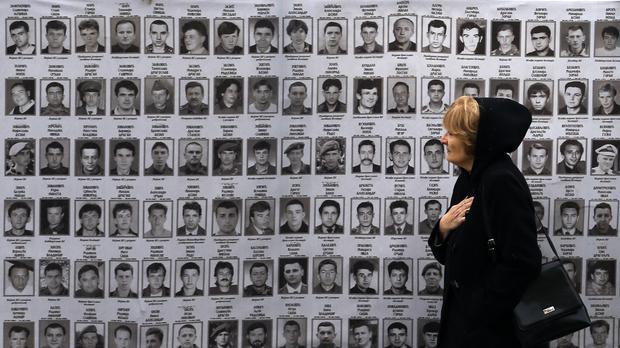 A woman walks in front of a banner of presumed victims at Serbia's war crimes court in Belgrade (AP)