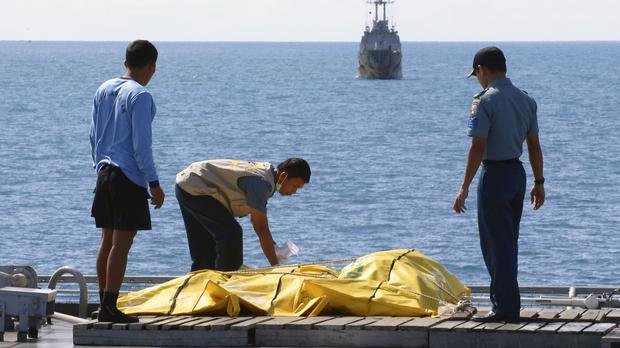 Crew members inspect bags containing bodies believed to be victims of AirAsia Flight 8501 on the deck of Indonesian Navy ship KRI Banda Aceh (AP)