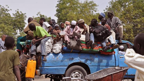 Villagers sit on the back of a pick-up truck as they and others flee the recent violence near the city of Maiduguri, Nigeria (AP)
