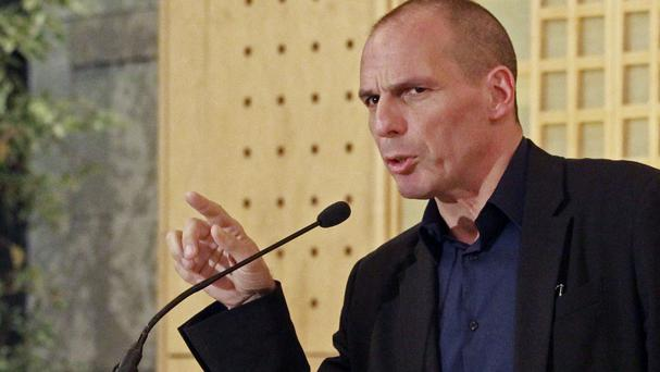 Greek Finance Minister Yanis Varoufakis addresses reporters after talks at the Economy Ministry in Paris (AP)