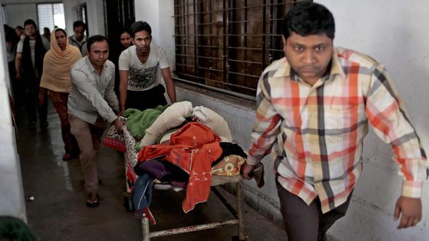 The victim of a recent bomb attack lies on a stretcher at a hospital in Dhaka (AP)