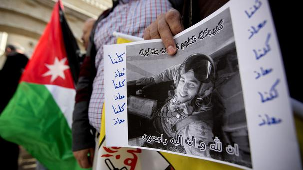 A poster of Jordanian pilot Muath al-Kaseasbeh is held during a protest in front of the Jordanian embassy (AP)