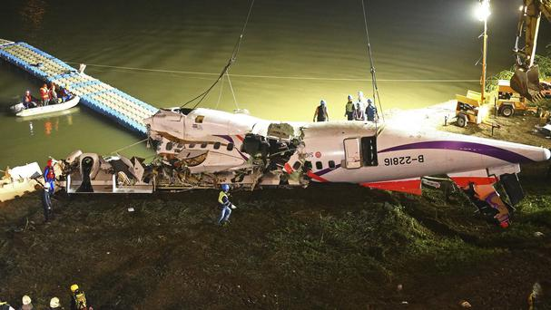 The mangled fuselage of a TransAsia Airways commercial plane is dragged to the river bank after it crashed in Taipei (AP)