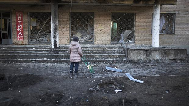A woman stands outside clinic 27, damaged after shelling, in Donetsk, Ukraine (AP)