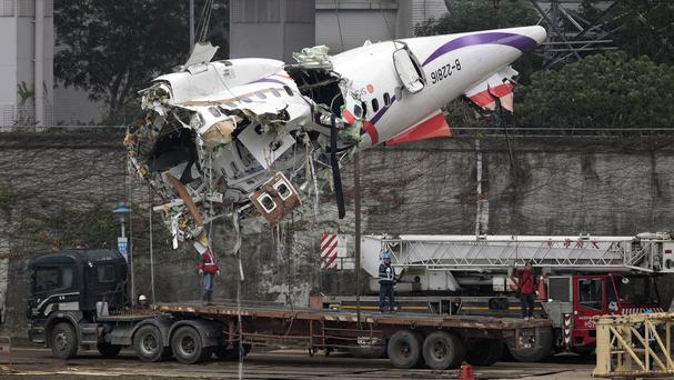 The main fuselage from TransAsia Airways Flight 235 is hoisted away in Taipei, Taiwan (AP)