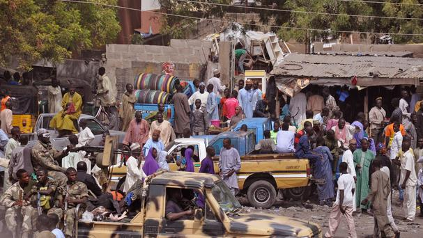 Soldiers pass by on the back of an armed truck as they patrol at a local market after recent violence in surrounding areas at Maiduguri, Nigeria (AP)