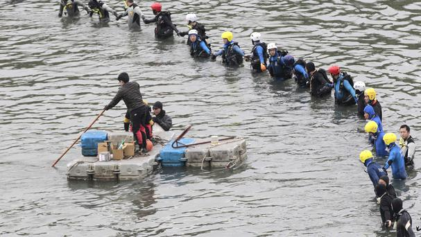 Divers continue to search a river for those missing after a commercial plane crash in Taipei, Taiwan (AP Photo/Wally Santana)