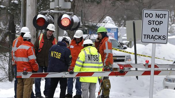 Emergency personnel examine the scene where an SUV was struck by a train (AP)