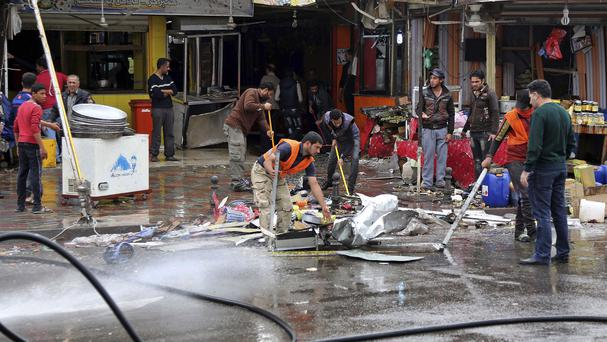 Iraqis clean up the site of a suicide bombing in the capital's south-eastern neighbourhood of New Baghdad. (AP)