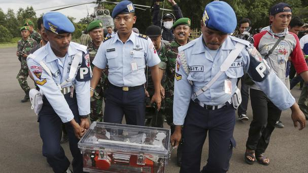 Indonesian air force personnel carry the flight data recorder of the ill-fated AirAsia plane that crashed in the Java Sea (AP)