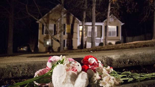 Flowers and teddy bears lie on the street outside the home where five people were shot dead (AP)