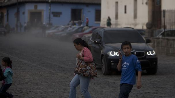 People cross a street covered with ash from the eruption of the Fuego Volcano at Antigua Guatemala. (AP)