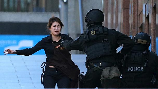 Bae Jie-un said she found it difficult to look at the iconic images of her clutching the arm of a police officer as she ran from the cafe (AP)