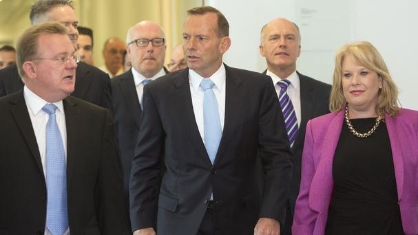 Tony Abbott leaves a meeting of the ruling Liberal Party, surrounded by supporters (AP)
