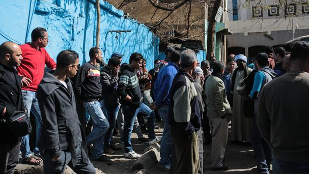 Friends and relatives of 22 football fans who were killed in Cairo wait outside a morgue. (AP)