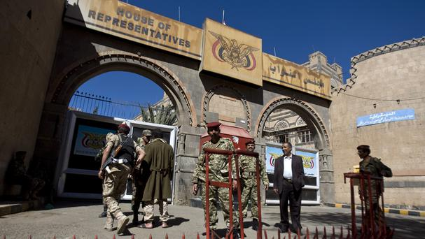 Houthi Shiite Yemenis wearing army uniforms stand guard outside parliament in Sanaa (AP)