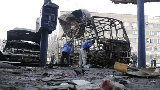 Organisation for Security and Cooperation in Europe officials investigate the scene after the bus station attack. (AP)