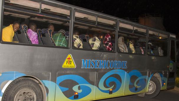 Rescued migrants sit on a bus after at least 29 died from hypothermia while travelling from North Africa on Sunday. (AP)