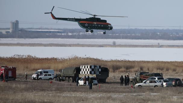 Rescue workers inspect the area where a Russian military jet crashed while on a training mission in the Volgograd region (AP Photo/Dmitry Rogulin)