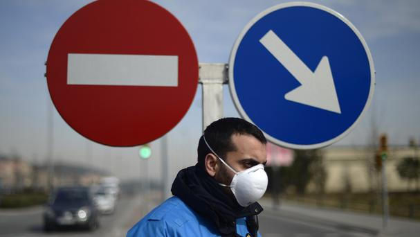A policeman wearing a mask blocks the entrance to the area after a chemical explosion in Igualada, Spain (AP)