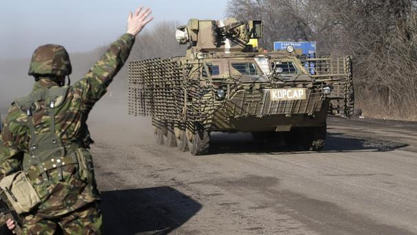 A Ukrainian government soldier waves to an armoured vehicle driving near the town of Artemivsk. (AP)