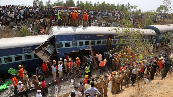 Rescuers and onlookers gather around damaged coaches of a derailed train near Anekal, about 40 kilometres south of Bangalore, India (AP)