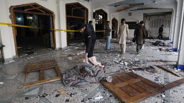 Pakistani security officials look for forensic evidence at a Shiite mosque attacked by militants in Peshawar. (AP)