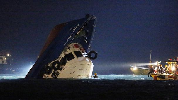 Rescuers check on a half submerged boat after it collided near Lamma Island, off the coast of Hong Kong. (AP)