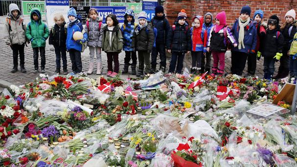 Schoolchildren look at flowers laid at a cultural centre in Copenhagen following attacks at the weekend.(AP)