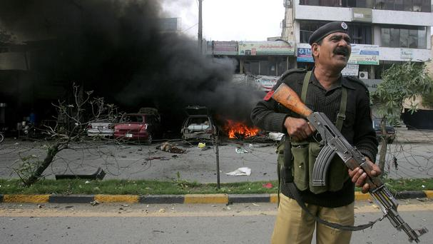 A Pakistani police officer stands guard at the site of the bombing in Lahore. (AP)