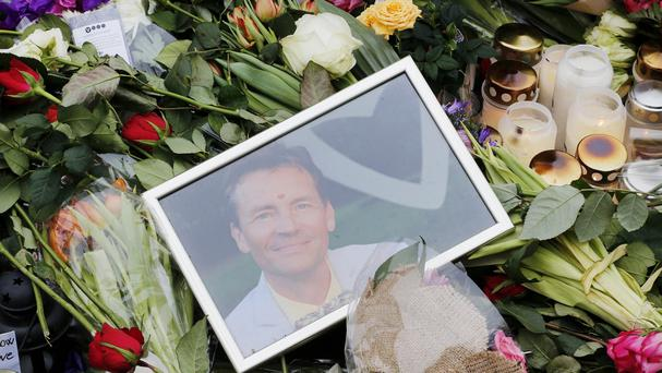A picture of film director Finn Noegaard, who was shot dead on Saturday, lies next to flowers left in Copenhagen. (AP)