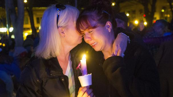 Tonya Castillo, left, comforts her daughter Tiffany Reid during a candlelight memorial for Kayla Mueller (AP/The Arizona Republic)