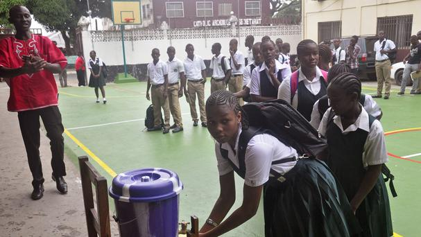 School children wash their hands before returning to classrooms as part of the Ebola prevention measures at Cathedral High School, Monrovia (AP)
