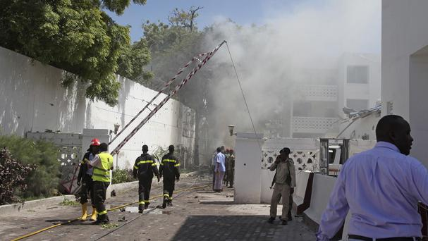 Smoke and steam from fires extinguished with water clouds the scene of a twin bombing attack on a hotel in the capital Mogadishu, Somalia (AP)