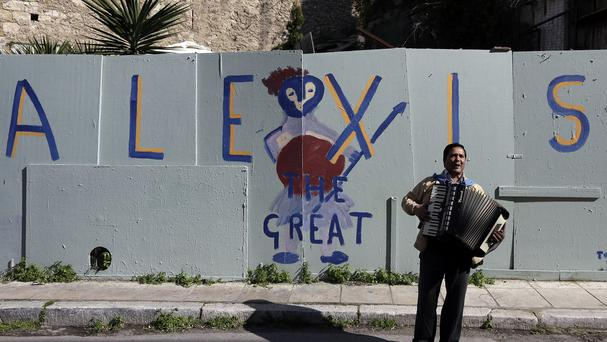 A busker plays music in front of a graffiti that refer to Greece's Prime Minister Alexis Tsipras in the traditional Plaka district of Athens (AP)