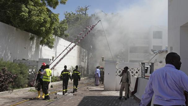 Smoke and steam from fires extinguished with water, clouds the scene of a twin bombing attack on a hotel in Mogadishu (AP)
