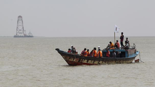 Bangladeshi rescuers search the River Padma after a ferry capsized with 140 people on board (AP)