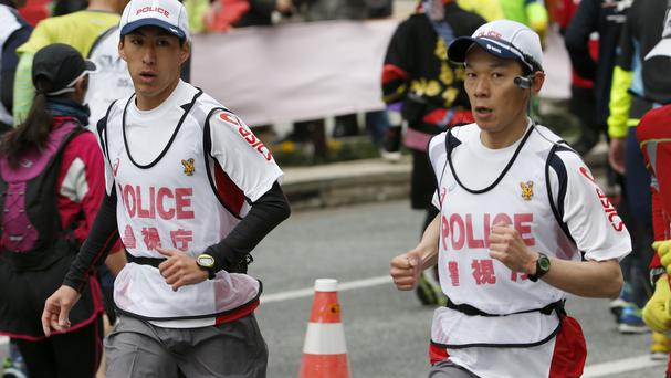 Tokyo's 'running police' follow competitors during the marathon in response to concerns over threats of terrorism