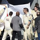 Medical staff hold sheets around Fernando Alonso as he is evacuated from the medical centre to the helicopter after crashing during F1 testing in Spain (AP)