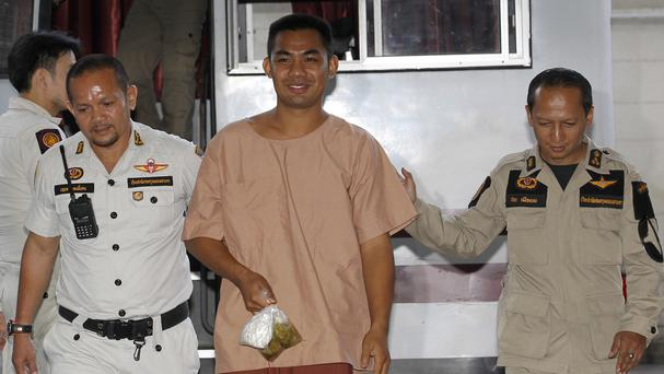 Patiwat Saraiyaem is escorted by Thai corrections officers upon arrival at Criminal Court in Bangkok (AP)