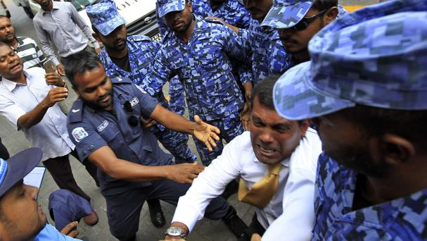 Maldives former president and current opposition leader Mohamed Nasheed tussles with policemen as he is brought before a court in Male (AP)