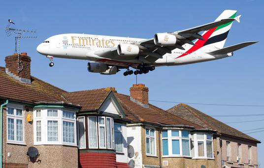 An Emirates Airbus A380 aircraft is seen above roof tops as it comes into land at Heathrow Airport in west London